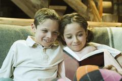 Preteen boy and girl reading book together - stock photo
