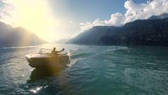 Happiness  lifestyle background. carefree man riding motorboat on lake at sunset Stock Footage