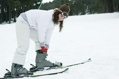 Young woman wearing skis, bending over to adjust boots Stock Photos