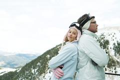 Two young skiers standing back to back, smiling, one looking at camera, portrait Stock Photos