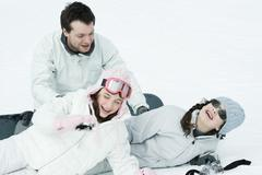 Young friends playing around in snow, laughing Stock Photos