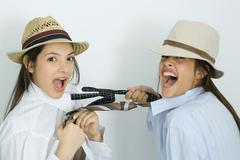 Two young female friends dressed in hats, pulling each other's ties, laughing at Stock Photos