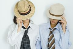 Two young friends pulling hats down over their faces, portrait Stock Photos