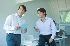 Two businessmen in office, one holding cell phone - stock photo