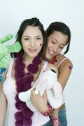 Two young female friends with stuffed animals, smiling at camera, portrait - stock photo