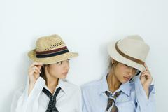 Two young friends pulling hats down over their faces, one looking at camera, Stock Photos