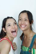 Two young female friends, one sticking tongue out, the other laughing, portrait Stock Photos