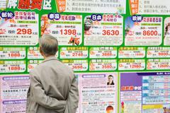 Man looking at ads on wall in Chinese, rear view Stock Photos