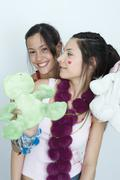 Two young female friends, one holding stuffed animals, looking at camera, - stock photo