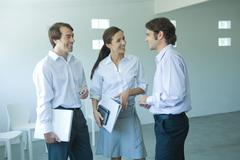 Three business associates chatting and smiling, three quarter length - stock photo