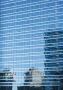 High rises reflected on facade of skyscraper - stock photo