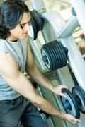 Man taking weight from rack - stock photo