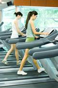 Two women walking on treadmills - stock photo