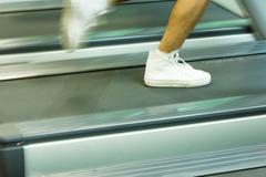 Man running on treadmill, close-up of feet Stock Photos