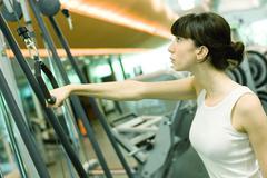 Woman pulling handle of exercise machine Kuvituskuvat