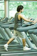 Man walking on treadmill - stock photo