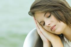 Teenage girl resting head on clasped hands, eyes closed, close-up Stock Photos