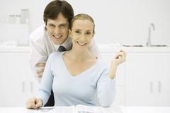 Couple in kitchen, smiling at camera, man leaning over woman's shoulder Stock Photos