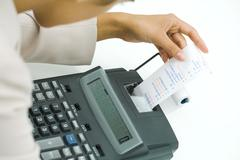 Businesswoman using adding machine, holding printout, cropped view Kuvituskuvat
