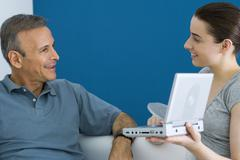 Teen girl showing her father portable DVD player, both smiling Stock Photos
