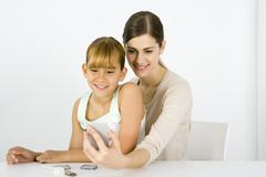 Girl sitting on young woman's lap, looking into hand mirror together - stock photo