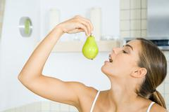 Woman holding up pear, head back, mouth open, side view Stock Photos