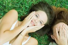 Mother and teen daughter lying together in grass, hands on face - stock photo