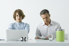 Teen boy at table with father, using laptop computer, man reading newspaper - stock photo