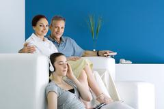 Family together in living room, parents smiling at camera, teen girl listening Stock Photos