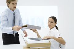 Professional woman handing binder to colleague from stack of many binders Stock Photos
