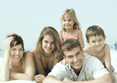 Family lying on beach, smiling, portrait Stock Photos