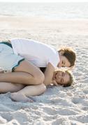 Preteen girls tickling each other in sand Stock Photos