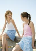 Preteen girls sitting on railing talking in beach setting Stock Photos