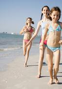 Girls running and walking on beach - stock photo