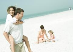 Family at the beach, man carrying teenage daughter piggyback while mother sits Stock Photos