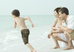 Family at the beach, parents watching son run towards water Stock Photos