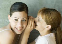 Girl whispering into young woman's ear - stock photo