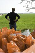Man standing by pile of garbage bags after cleanup effort, rear view Stock Photos