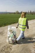 Volunteer carrying garbage full of trash outdoors - stock photo