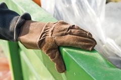 Gloved hand holding onto edge of dumpster Stock Photos