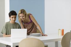 Teenage boy showing mother laptop computer Stock Photos