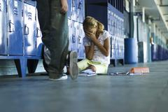 Female junior high student sitting on floor holding head in hands, boy standing Stock Photos