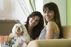 Mother and teenage daughter with pet dog, portrait - stock photo