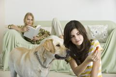 Teenage girl offering dog biscuit to pet dog - stock photo