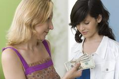 Mother giving teenage daughter pocket money Stock Photos