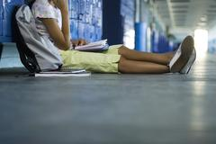 Junior high student sitting on hall floor leaning against lockers reading book Stock Photos