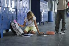 Junior high student picking up dropped school supplies, boy standing by watching Stock Photos