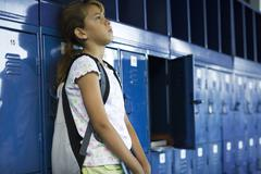 Female junior high student leaning against lockers contemplatively looking away Stock Photos