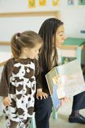 Teacher reading book aloud, child standing nearby Stock Photos