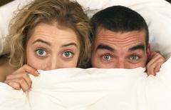 Startled young couple in bed holding sheet over their faces looking up at camera Stock Photos